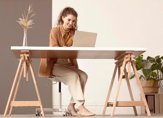 Colpo lungo di persona seduta e che lavora al computer portatile Foto Premium
