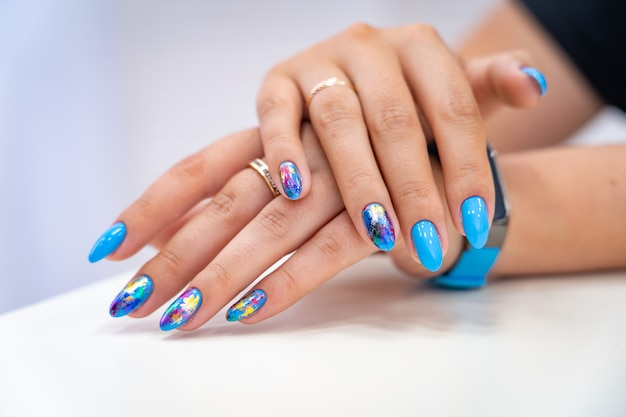 Molte mani di manicure con lucentezza colorata hanno diverse macchie in una luce Foto Premium