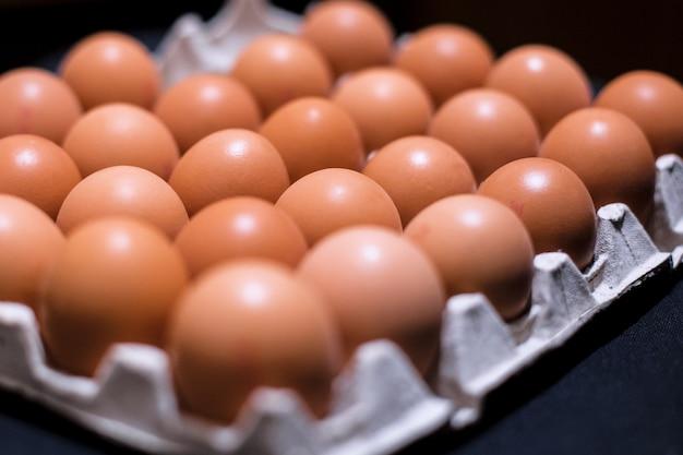 Molte uova di gallina in un vassoio della carta Foto Premium