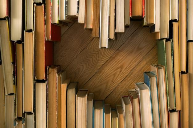 Amore concetto di forma di cuore da vecchi libri vintage sul pavimento di legno. Foto Premium