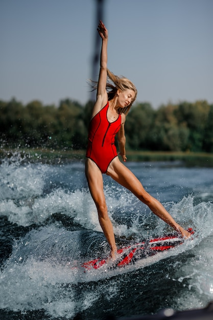 Donna bionda adorabile che pratica il surfing a bordo giù l'acqua blu Foto Premium