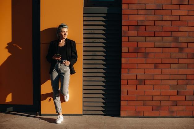 Bella signora alla moda con i capelli blu è sdraiata sul muro mentre tiene un cellulare e indossa gli occhiali Foto Premium