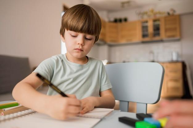 Angolo basso del bambino che attinge taccuino mentre istruito a casa Foto Premium