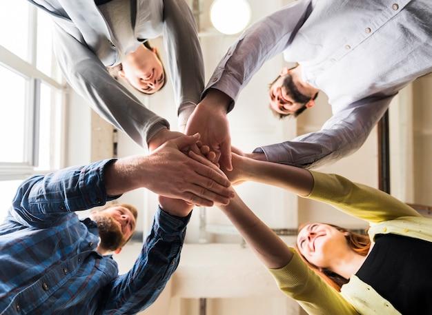 Punto di vista di angolo basso delle persone di affari che impilano mano insieme nel luogo di lavoro Foto Premium