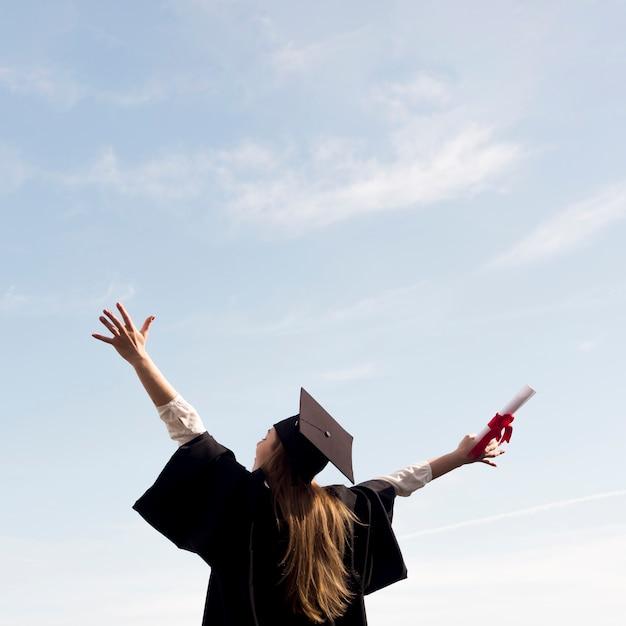 Giovane donna di angolo basso che celebra la sua laurea Foto Premium