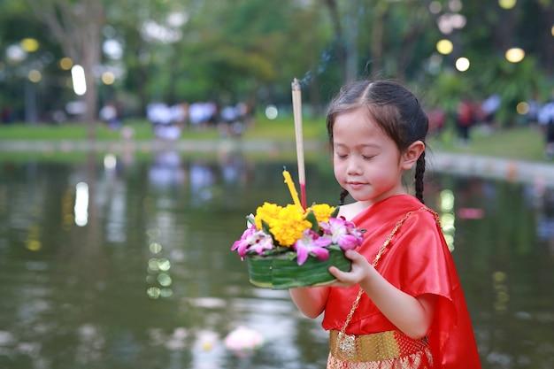 Festival di loy krathong, ragazza asiatica del bambino in vestito tradizionale tailandese Foto Premium