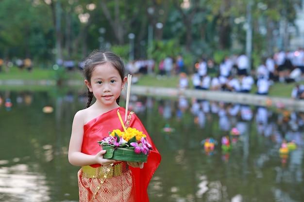 Festival di loy krathong, ragazza del bambino in vestito tailandese che tiene krathong per celebrare festival dentro Foto Premium