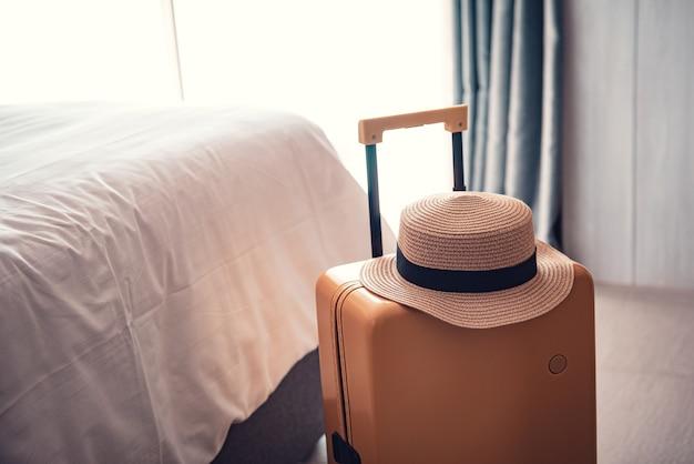 Borsa da viaggio con cappello in una camera d'albergo. Foto Premium