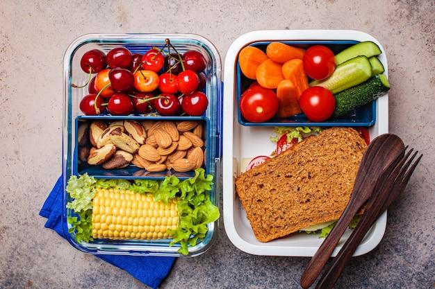 Scatola di pranzo con cibo fresco e sano. sandwich, verdure, frutta e noci in contenitori per alimenti, sfondo scuro. Foto Premium
