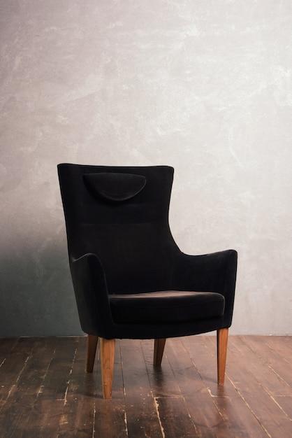 Lussuosa poltrona in velluto nero si trova vicino alla parete strutturale su un pavimento di legno scuro Foto Premium