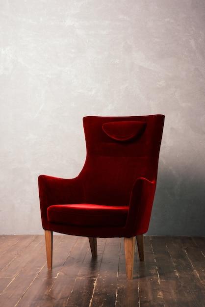 Lussuosa poltrona in velluto rosso si trova vicino alla parete strutturale su un pavimento di legno scuro Foto Premium