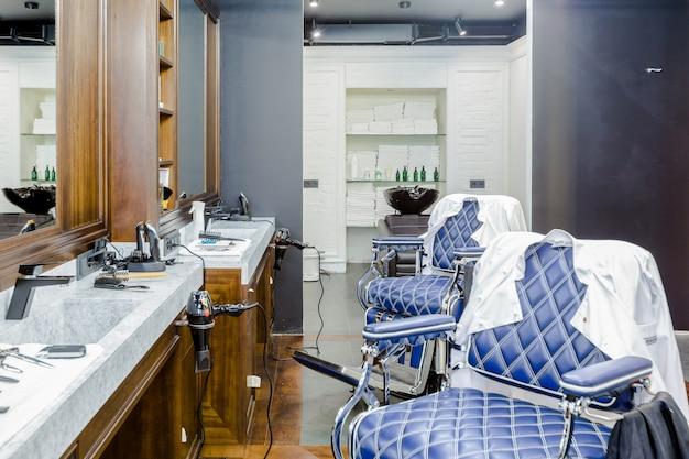 Interno del negozio di barbiere di lusso, mobili costosi blu, finiture in legno, soffitto nero alla moda Foto Premium
