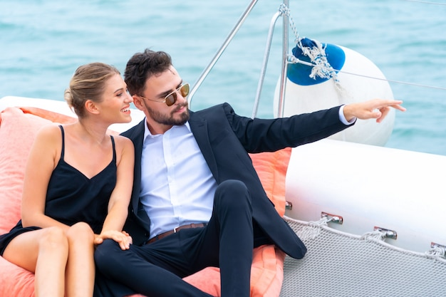 Il viaggiatore di rilassamento di lusso delle coppie in vestito e suite piacevoli si siede sul sacchetto di fagiolo nella parte dell'yacht di crociera con fondo del mare e del cielo bianco. viaggi d'affari di concetto. Foto Premium