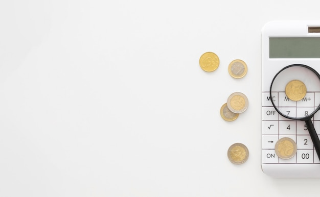 Lente di ingrandimento sulla calcolatrice con copia spazio e monete Foto Premium