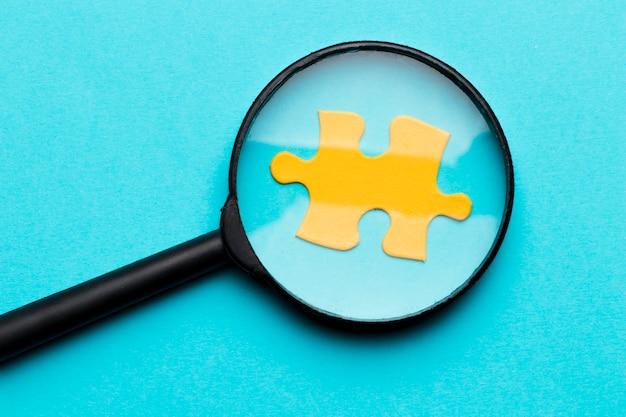 Lente d'ingrandimento sopra il pezzo di puzzle giallo su sfondo blu Foto Premium