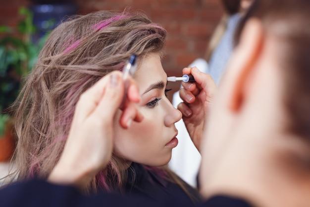 Make-up artist che fissa le sopracciglia della modella con il gel Foto Premium