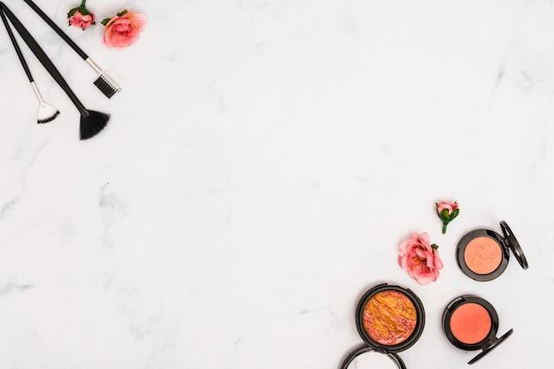 Pennelli per il trucco; rose e faccia cipria compatta su sfondo bianco con copia spazio per scrivere il testo Foto Premium