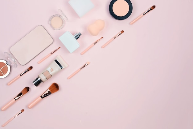 Trucco cosmetico decorativo, pennelli, strumenti e accessori su sfondo rosa pastello. Foto Premium