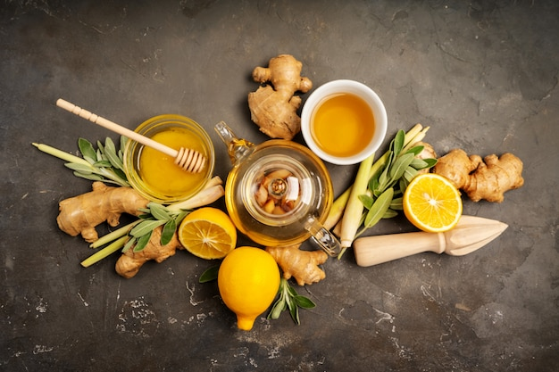 Preparare un tè antiossidante e antinfiammatorio sano con zenzero fresco, citronella, salvia, miele e limone su sfondo scuro con spazio di copia. vista dall'alto. Foto Premium