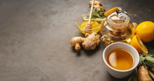 Preparare un tè antiossidante e antinfiammatorio sano con zenzero fresco, citronella, salvia, miele e limone su sfondo scuro con spazio di copia. Foto Premium