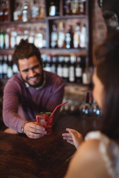 Barista maschio che serve un cocktail drink al cliente al bancone del bar Foto Premium