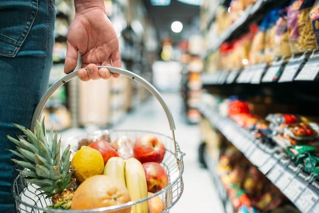 Mano maschio del cliente con cesto di frutta, persone che scelgono il cibo nel supermercato. shopping in drogheria Foto Premium