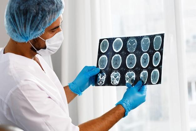 Il medico maschio esamina la risonanza magnetica cerebrale di un paziente Foto Premium