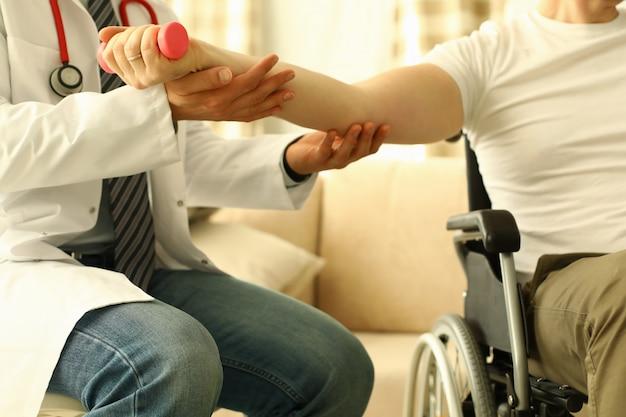 Medico maschio aiuta a sollevare il manubrio al concetto di terapia di riabilitazione del paziente disabile. Foto Premium
