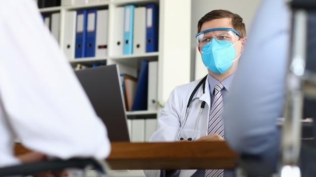 Medico maschio che guarda sospettosamente il paziente sospetta una fase grave del virus Foto Premium