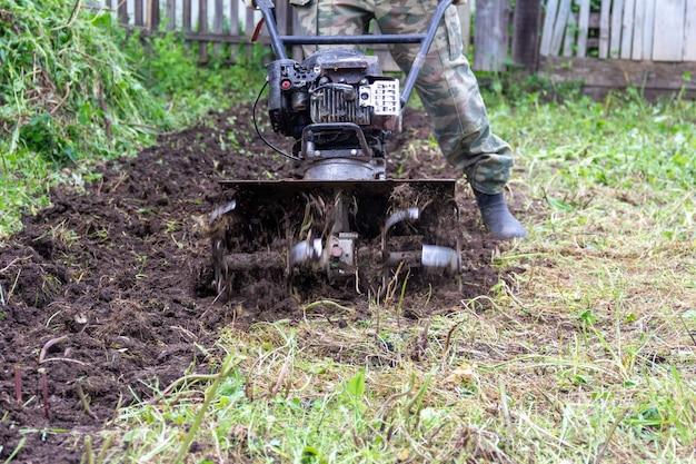 Un agricoltore maschio ara la terra con un trattore a benzina che prepara per piantare i semi nella fine di giorno di primavera su Foto Premium
