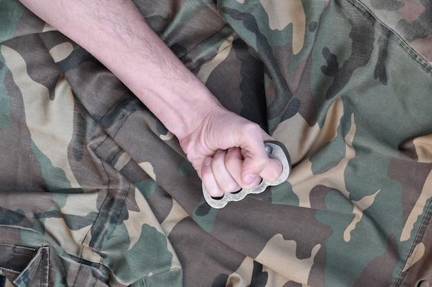 Pugno maschio con tirapugni sulla parete di una giacca mimetica. il concetto di cultura skinhead, armi da mischia fatte a mano Foto Premium