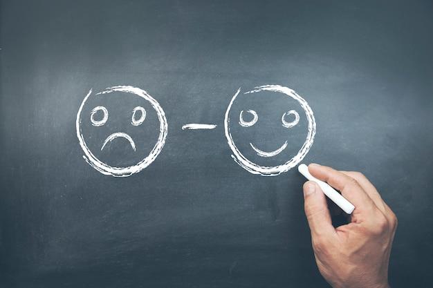 Mano maschio che disegna i fronti di smiley infelici e felici sulla lavagna Foto Premium