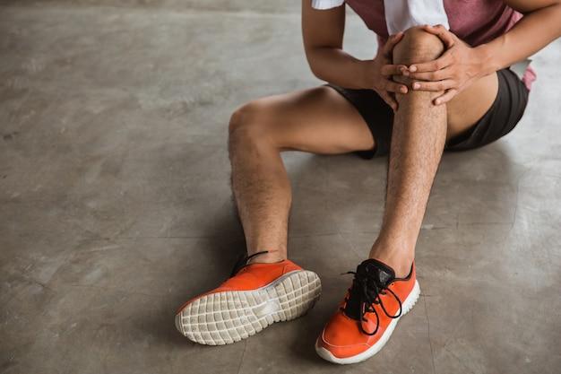 Mano maschio che tiene ferita al ginocchio Foto Premium