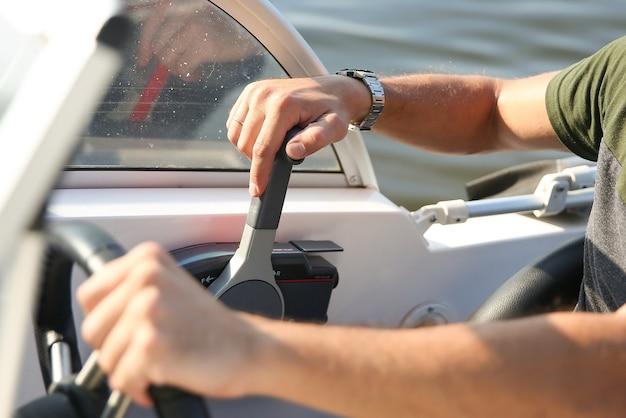 Mano maschio è sulla leva di comando di una fine bianca barca a motore Foto Premium