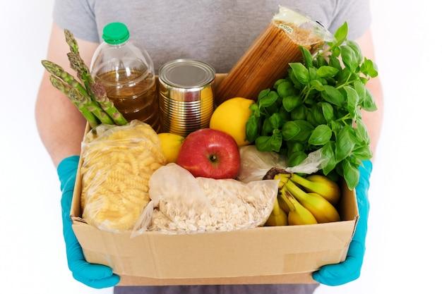 Mani maschili in guanti di gomma medica tengono una scatola di cartone con prodotti. olio di semi di girasole, conserve alimentari, pasta, farina d'avena, riso, frutta e verdura. consegna del cibo, donazione di cibo Foto Premium