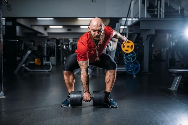 Sollevatore maschio che fa esercizio con manubri in palestra Foto Premium