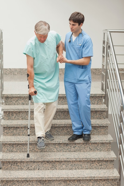Infermiere maschio che assiste un paziente sulle scale Foto Premium