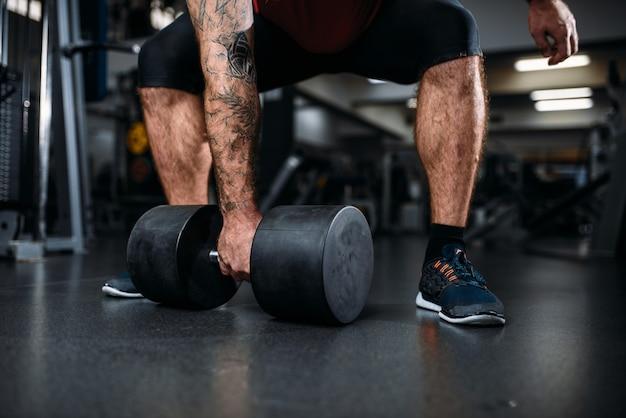 Persona di sesso maschile che fa esercizio con manubri, allenamento in palestra. Foto Premium