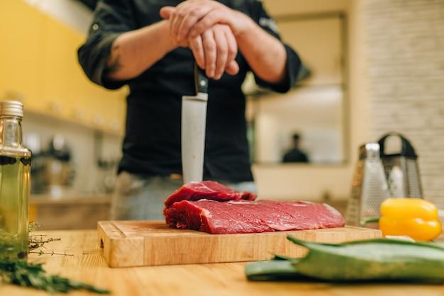 Persona di sesso maschile con coltello e pezzo di carne cruda su tavola di legno Foto Premium