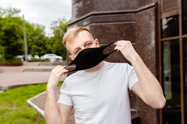 Ritratto maschile. un uomo con una maschera nera. quarantena in città. Foto Premium