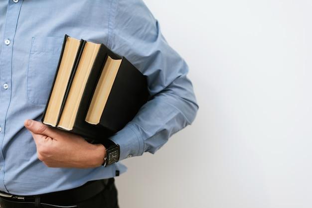 Uno studente maschio in camicia blu e pantaloni eleganti tiene una pila di libri. il concetto di formazione, ricerca di idee, soluzioni di business Foto Premium