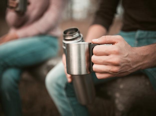 Mano maschile con tazza e thermos, pausa campeggio Foto Premium