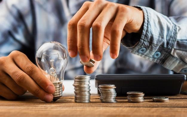 Uomo che allinea le monete di risparmio sulla tavola Foto Premium