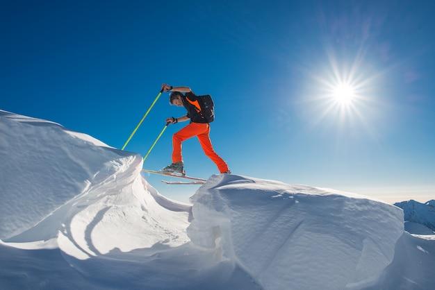 Un uomo sciatore alpino arrampica su sci e pelli di foca in così tanta neve con ostacoli Foto Premium