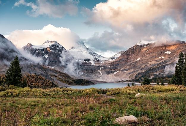 Viaggiatore con zaino e sacco a pelo dell'uomo che cammina sul campo nel parco provinciale di assiniboine di mattina Foto Premium
