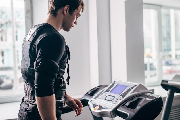 Uomo in abito nero per ems formazione sul tapis roulant Foto Premium