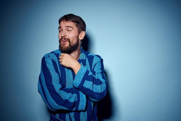 Un uomo in una veste blu su un gesto leggero con le sue mani modella abiti da casa. Foto Premium