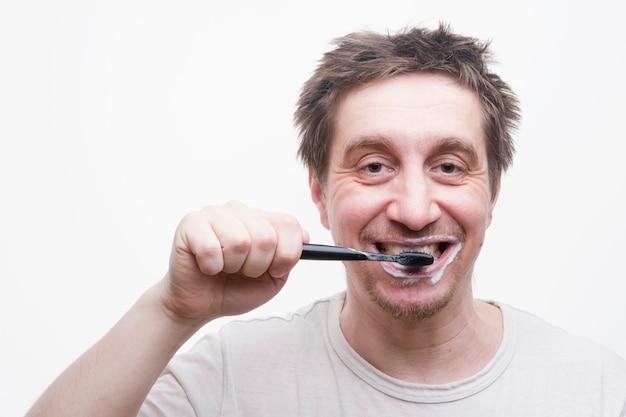 Un uomo si lava i denti dopo aver mangiato su uno sfondo bianco Foto Premium