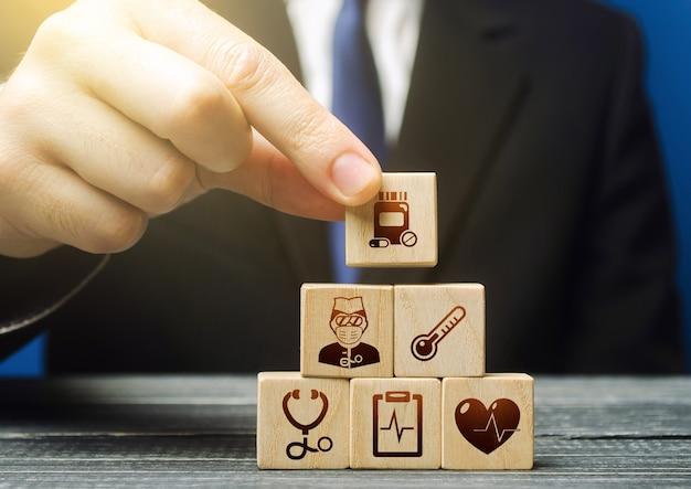 L'uomo costruisce una piramide a blocchi con i simboli delle icone mediche Foto Premium