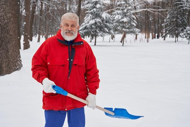 Neve di pulizia dell'uomo con la pala in parco. Foto Premium